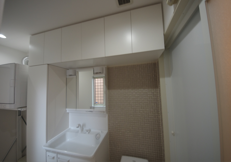 細長い洗面室を有効に使うための、洗面台と収納棚
