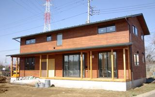深緑色の薄い屋根と、柿渋色の杉板の外壁